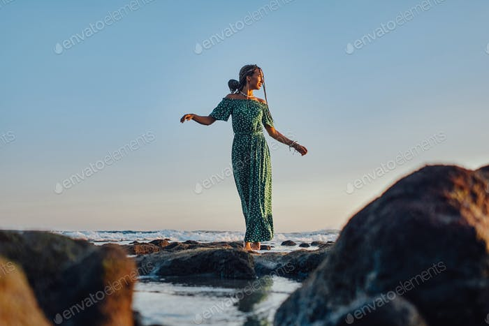 Woman walking on beach in bali at sunset