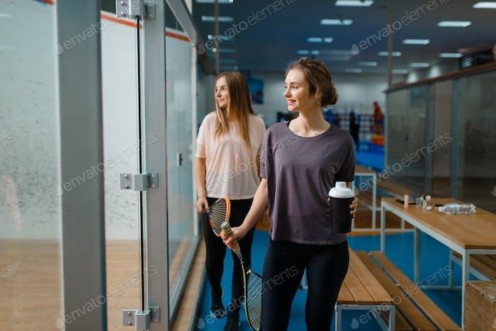 Zwei lächelnde weibliche Squash-Spieler im Fitnessstudio