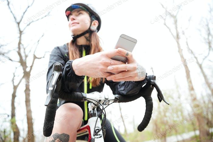Nachdenkliche Frau auf dem Fahrrad mit Handy im Park