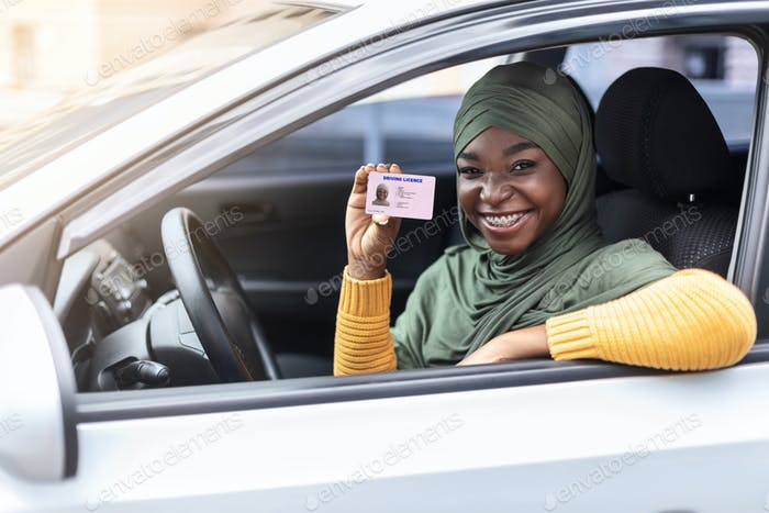 Happy black muslim woman in hijab sitting in car, showing driver license