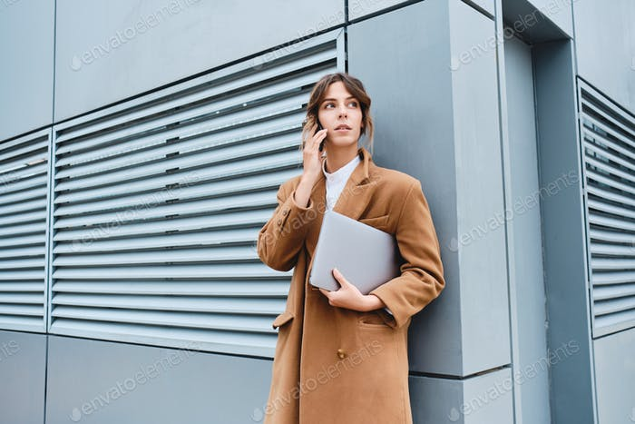 Young confident businesswoman in coat with laptop talking on cellphone outdoor