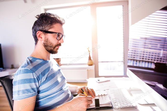 Architect working from home on computer, writing, taking notes