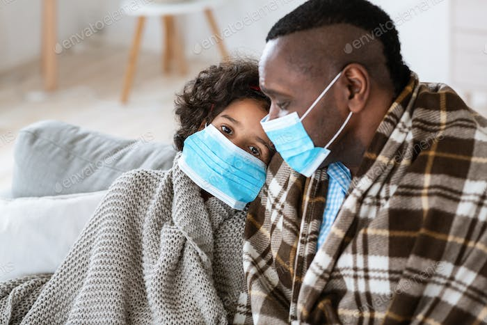 Worldwide disease outbreak. Mature man with his granddaughter wearing medical masks at home