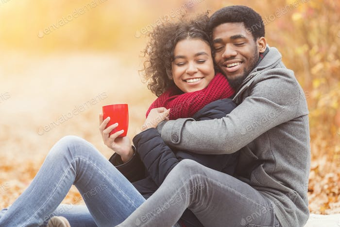 African couple in love embracing and drinking coffee in park