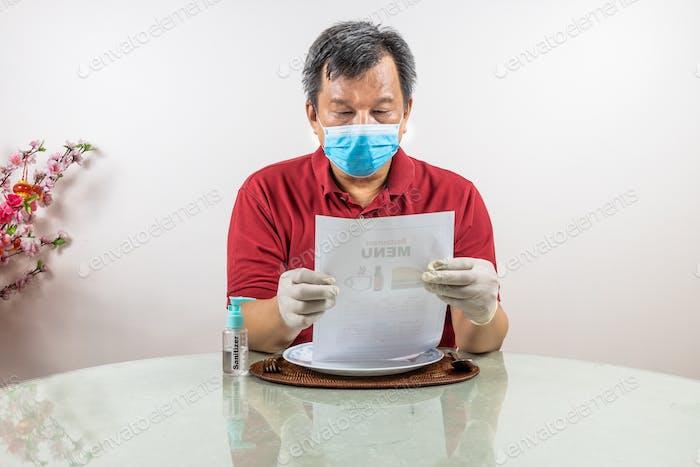 Homem asiático com máscara facial, luva, desinfetante jantar no restaurante, como parte do novo estilo de vida normal