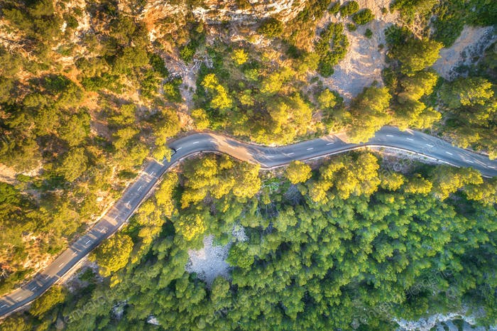 Aerial view of mountain curve road with cars, green forest