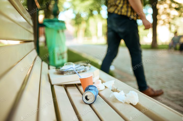 Man left trash on the bench in park, ecology care