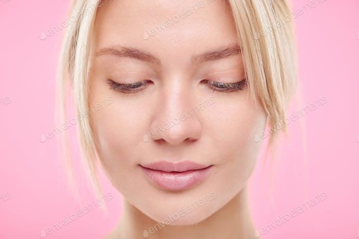 Pretty young blond natural woman looking down over pink background