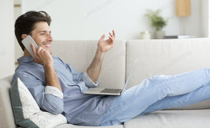 Careless Guy Talking On Cellphone Working On Laptop At Home