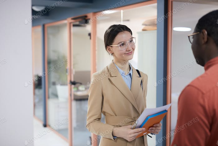 Smiling Young Businesswoman Looking at Colleague