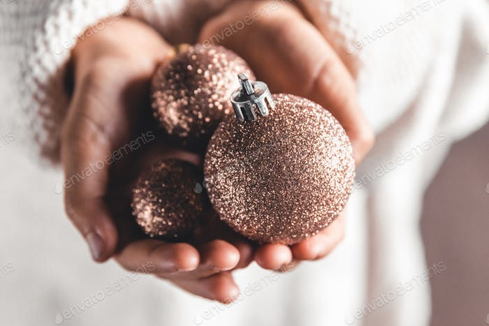 A child holding red Christmas ball. Christmas card design. Copy space. Close-up