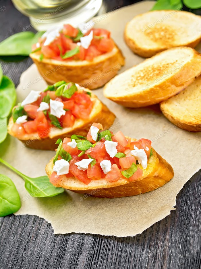 Bruschetta with tomato and cheese on wooden board