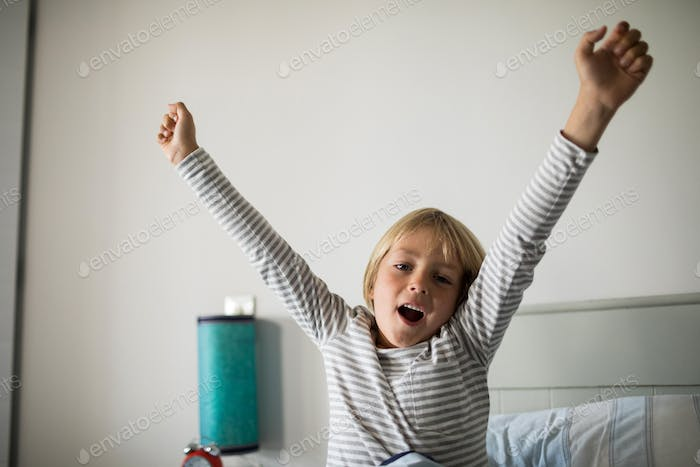 Boy yawning on bed in the bedroom at home