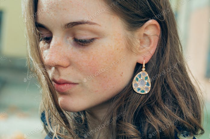 Young woman spring street portrait with freckles happy and beautiful. Girl style coat with jewelry.