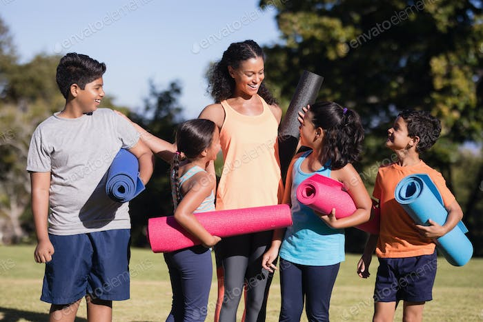Happy children with instructor holding mats