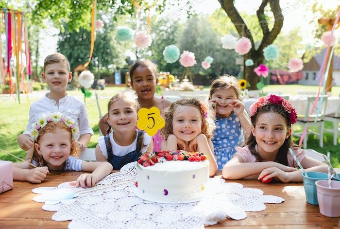 Kids birthday party outdoors in garden in summer, celebration concept