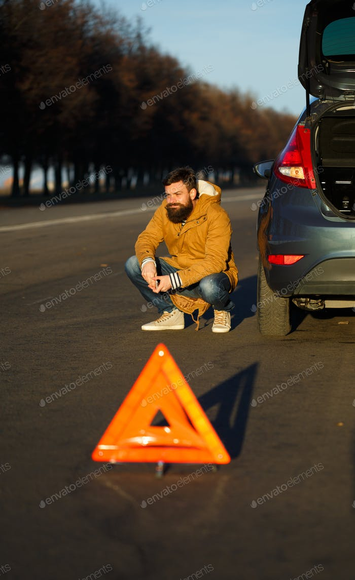 Man examining damaged automobile cars after breaking