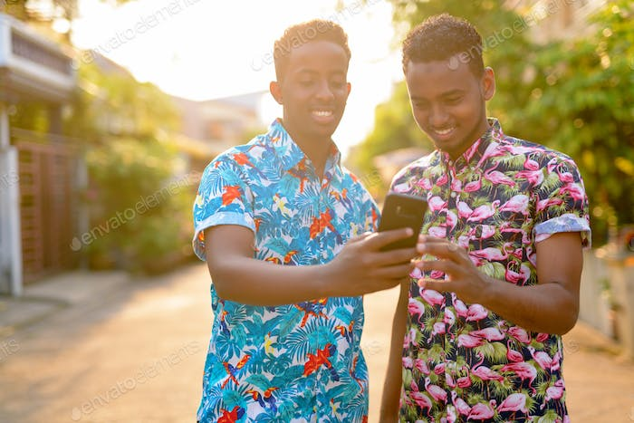 Two happy young African tourist men using phone together outdoors