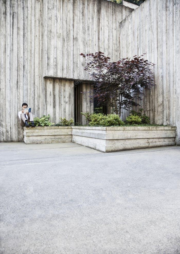 Businessman taking a break in a city park alcove.