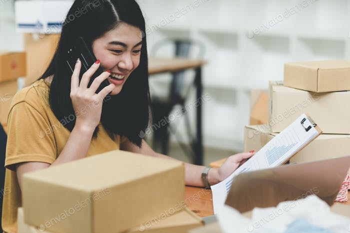 Woman selling products online talking on the phone and checking stock,Sell online.