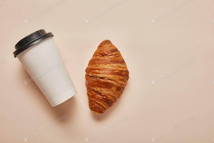 Draufsicht auf Kaffee zum Go und leckeres Croissant auf beigem Hintergrund