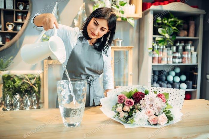 Florist gießt Wasser in eine Vase in Blumenboutique
