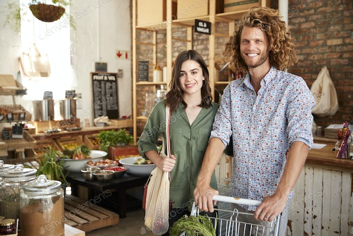 Portrait Of Couple With Trolley Buying Fresh Fruit And Vegetables In Plastic Free Grocery Store