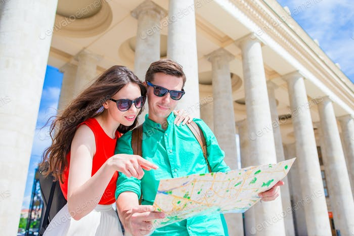 Young couple traveling on holidays in Europe smiling happy. Caucasian family with city map in search