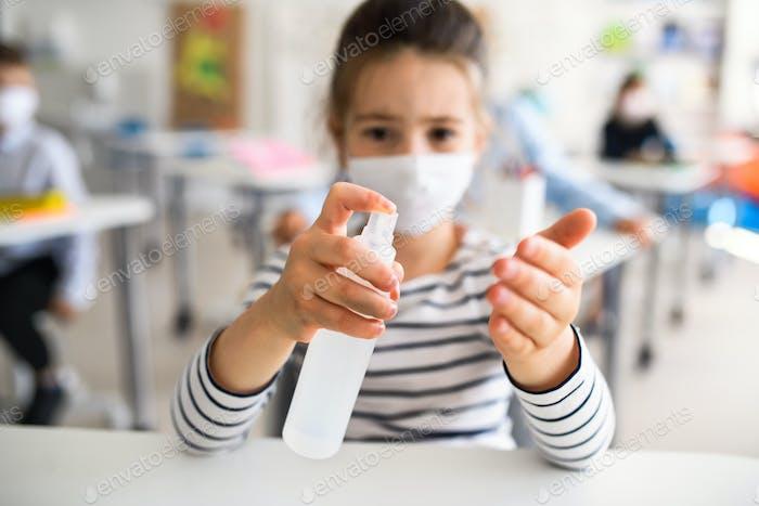 Kleines Mädchen mit Gesichtsmaske in der Schule nach covid-19 Lockdown, desinfizierende Hände