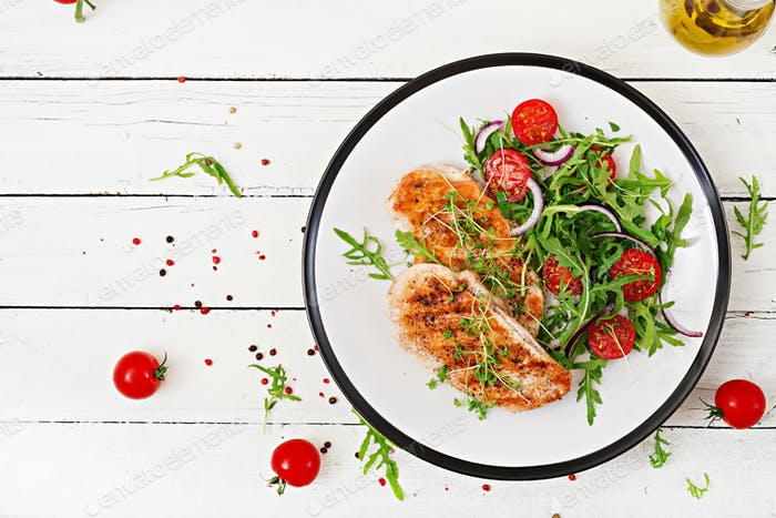 Grilled chicken fillet and fresh vegetable salad of tomatoes,red onion and arugula.