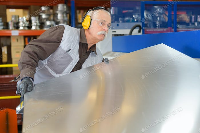Senior man moving sheet metal