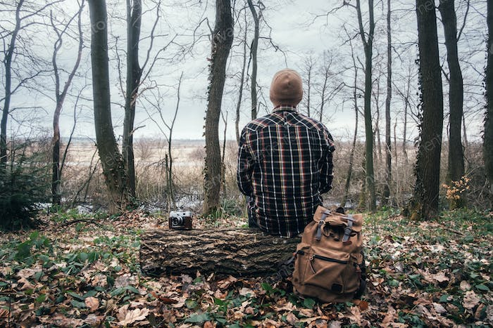 Man with backpack in wild forest