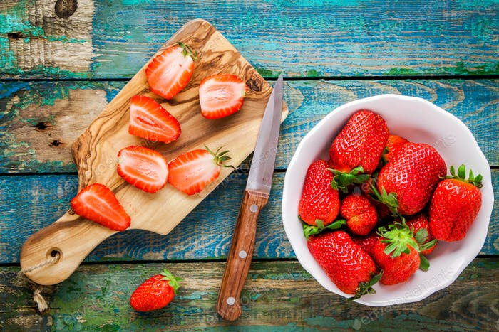 Fresh ripe organic strawberries in a white bowl and sliced on th