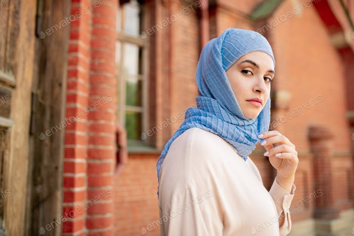 Young serious Arabian female in blue hijab chilling out in ancient city