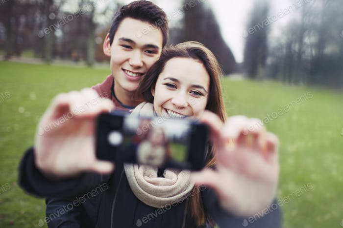 Young couple looking happy taking self portrait