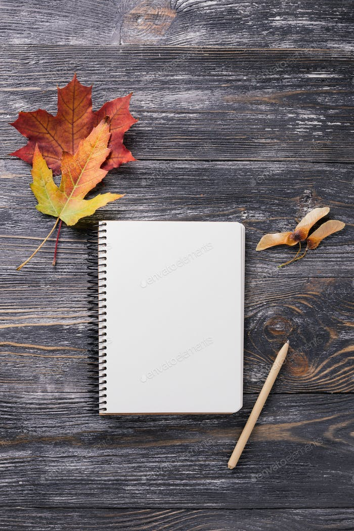 Paper Notebook with Autumn Leaves on Wooden Background.