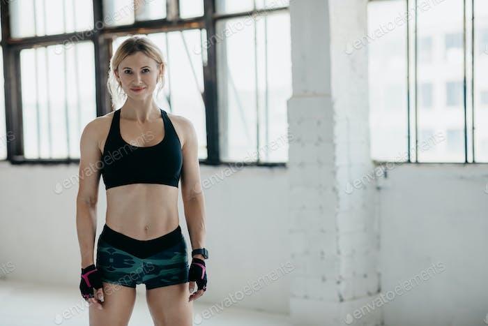 Muskulärer, starker und schöner Körper. Lächelnde Frau mittleren Alters in Sportbekleidung mit Smartwatch und