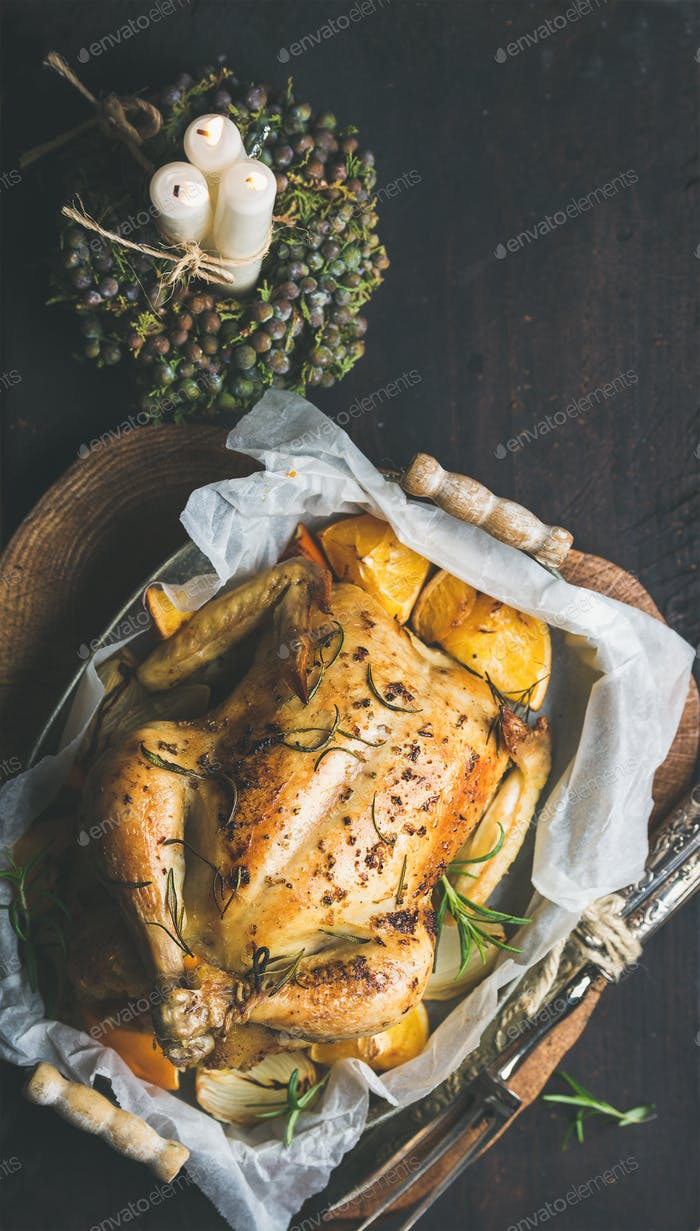 Christmas dinner with roasted chicken, rosemary and decorative candles