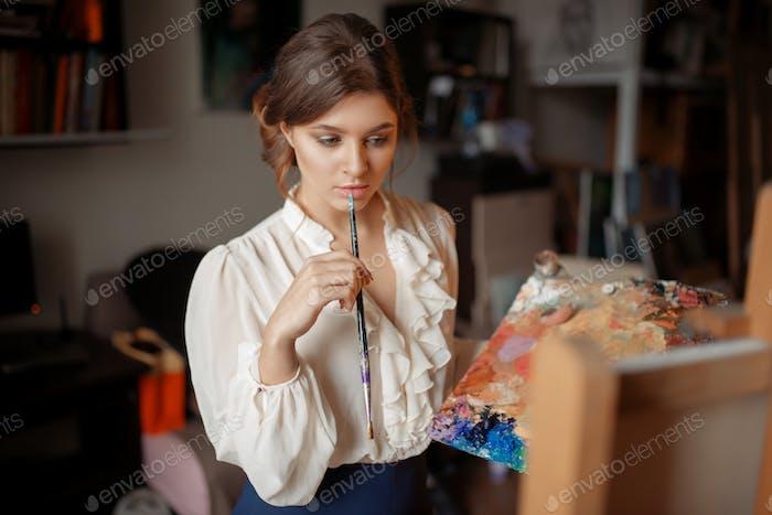 Nachdenkliche weibliche Malerin mit Farbpalette