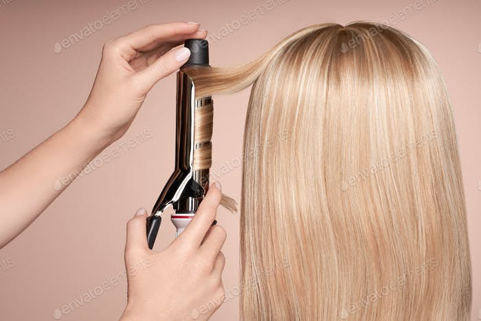 Der Friseur lockt lange Haare mit einem Lockenstab