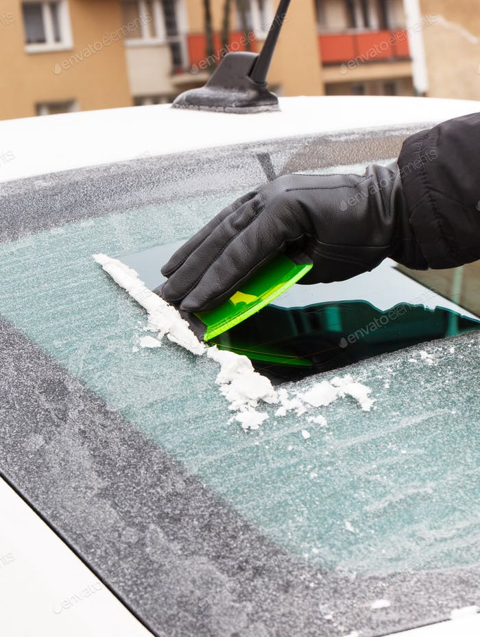 Hand in glove scraping ice or snow from car windscreen, winter problems in transportation concept