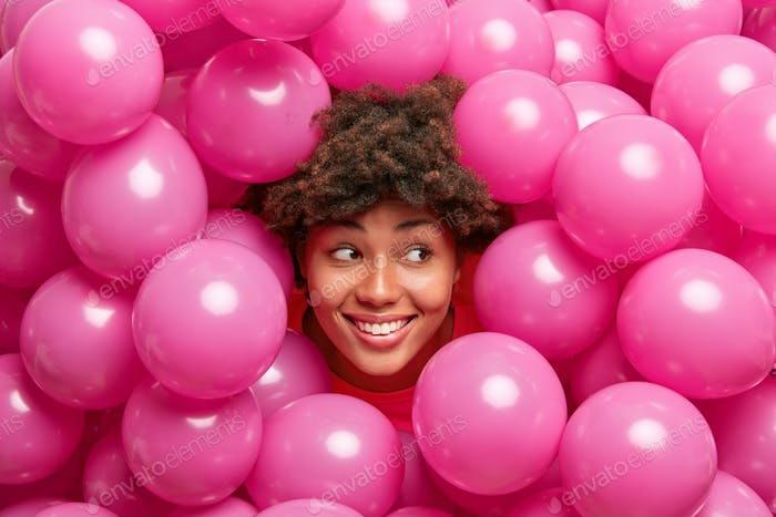 Happy cute young African American woman with curly bushy hair smiles broadly looks right has festive