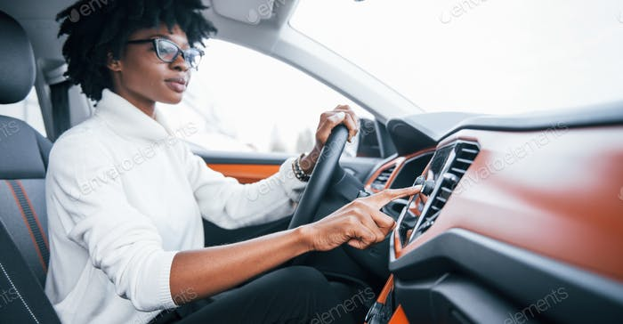 Young african american woman sits inside of new modern car