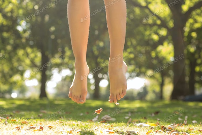 Close up of female feet jumping in the air in a park on a sunny day