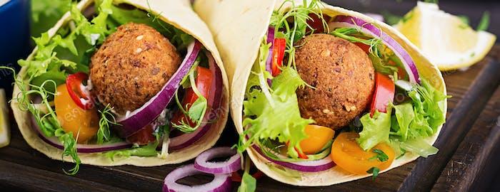 Tortilla wrap with falafel and fresh salad. Vegan tacos. Vegetarian healthy food. Banner
