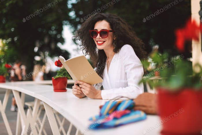 Smiling curly lady in sunglasses with notepad in hands happily resting at summer terrace of cafe