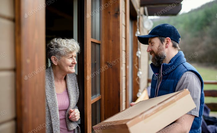 Man courier delivering parcel box to senior woman