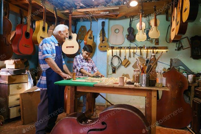 Lute Maker Grandpa Teaching Grandson Chiseling Wood