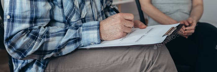 Man in a blue checked shirt and grey pants sits on a chair and holds a writing pad on his lap
