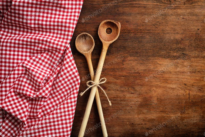 Wooden kitchen utensils on red checkered tablecloth on wooden table, top view, copy space